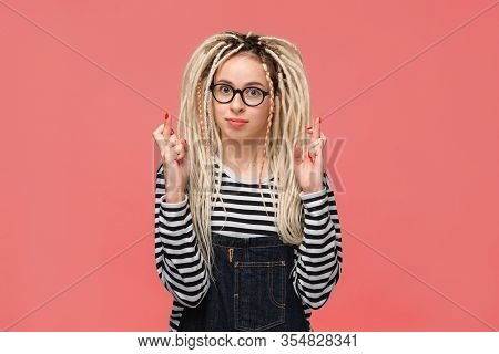 Portrait Of A Young Girl With Long Dreads Standing Over Pink Background Holding Fingers Crossed For
