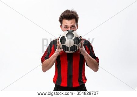 Confident Soccer Player In A Red Sportswear Holding Soccer Ball Infront Of His Face And Looking At T