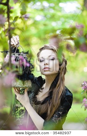 Beautiful Witch with a strange cage in his hands