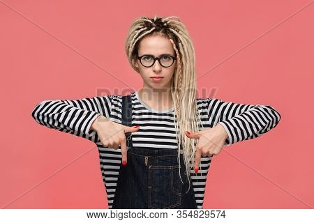 Beautiful Young Girl With Dreadlocks In A Striped Shirt And Jeans Jumpsuit Pointing With Two Fingers