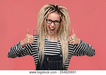 Beautiful Young Girl With Dreadlocks In A Striped Shirt And Jeans Jumpsuit Smiling Holding Thumbs Up