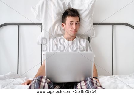 Handsome Young Man In The White Shirt And Pajama Sitting On A Bed With A Pillow Behind His Back Hold