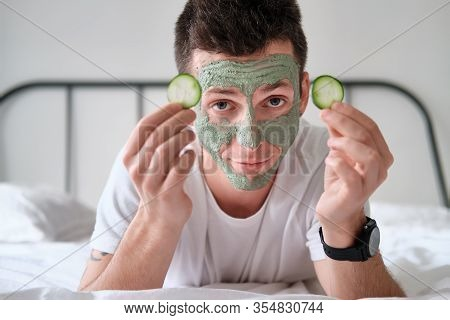 Young Man In A White Shirt With Applied Green Cosmetic Mask Holding Pieces Of Cucumber Relaxing On A