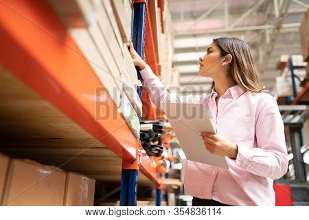 Young Attractive Employee Examining Box In Rack While Holding Inventory Clipboard At Factory