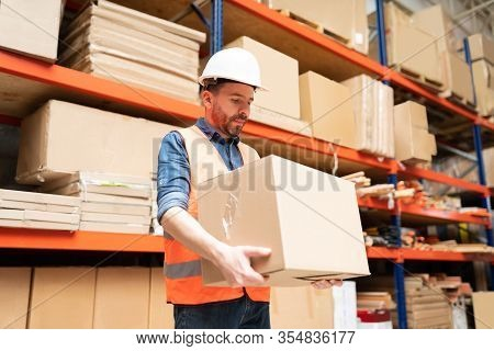 Low Angle View Of Handsome Male Worker Carrying Cardboard Box Against Rack At Warehouse