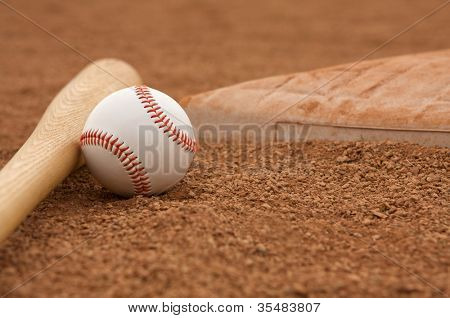 Baseball & Bat on the Infield Dirt near a base