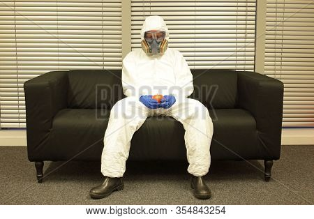 Quarantine  - food supply chain problems.Professional in protective clothing, mask and gloves, sitting on the sofa  with last apple in  hands.