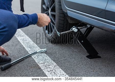Close Up Of Repair Of A Flat Tire. Man Lifts Up A Car Using A Jack For Wheel Replacement. Replacing