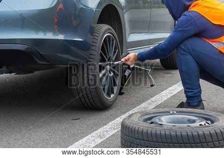 A Man In A Orange Safety Vest Changes A Flat Tire On A Road. Closeup Mans Hands To The Wheel Of A Br