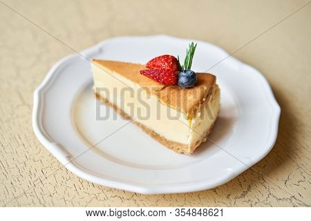 Closeup Piece Of Delicious Cheesecake With Strawberry And Mint Leaves On White Plate.