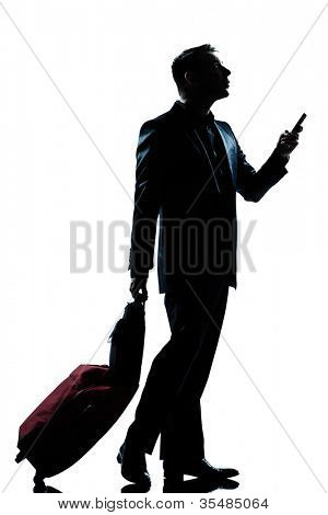one caucasian business traveler man walking on the phone with suitcase  full length silhouette in studio isolated white background
