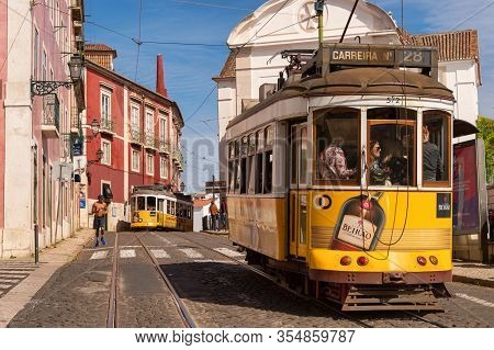 Lisbon, Portugal - 8 March 2020: Tourists Riding The Famous Yellow Tram 28 In Alfama District