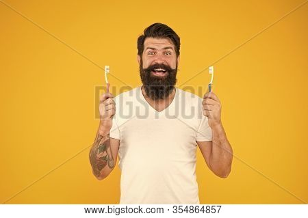 Bearded Man Holds Toothbrushes Yellow Background. Guy Holds Two Toothbrushes. Hipster Happy Smiling