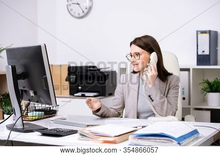 Pretty young secretary sitting by desk in front of computer monitor while discussing data with client on the phone