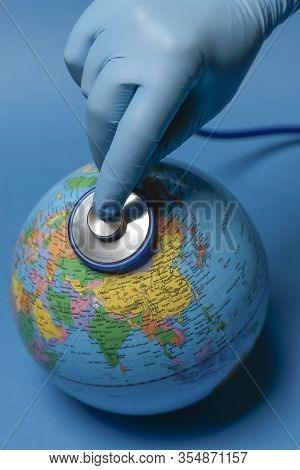 Vertical View Of A Hand With Nitrile Blue Glove Using A Stethoscope To Auscultate The Terrestrial Gl