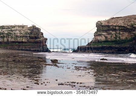 Two Large Rocky Cliffs On A Sandy Beach At Natural Bridges State Beach Park, Santa Cruz, California,