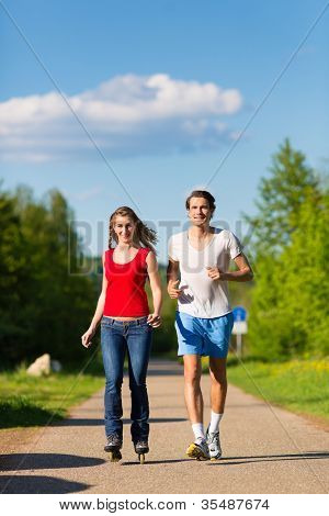 Young couple - man and woman - doing sports outdoors, he is jogging while she is roller blading