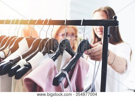 Woman Fashion Clothes Of Different Colors Clothing On Hangers At The Showroom / Shopping Women Choos