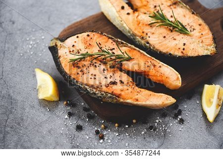 Grilled Salmon Steak With Herbs And Spices Rosemary Lemon On Wooden Cutting Board Background / Close