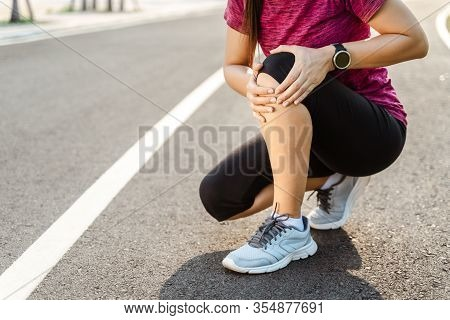 Knee Injuries. Sport Woman With Strong Athletic Legs Holding Knee With Her Hands In Pain After Suffe