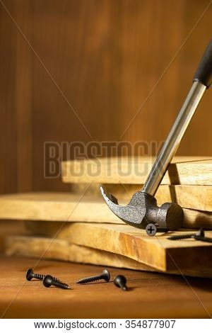 Hammer And Screw On Lumber In Lighting And Shadow Of The Sunshine In Morning. The Concept Of Woodcra