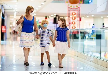 Family Wearing Face Mask In Shopping Mall In Asia