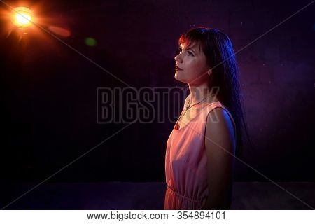 Portrait Of A Girl In Pink Dress In The Light Of Colored Lamps Red, Bright Light And Outline Blue Co