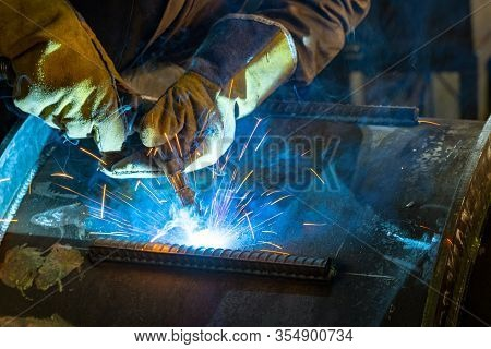 Welder Working With Electrode At Semi Automatic Arc Welding In Manufacturing Production Plant. Weldi