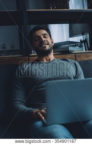 Handsome Young Man Masturbating While Watching Pornography On Laptop On Sofa In Living Room