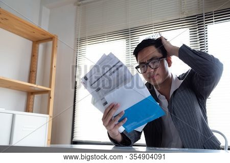 Sad Confused And Stressed Of Young Asian Man Holding Bills Letter Of Credit Card Debt, Financial Mon