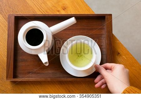 Woman Holding White Cup With Japanese Green Tea And Teapot On Dark Wooden Serving Tray On Table, Abo