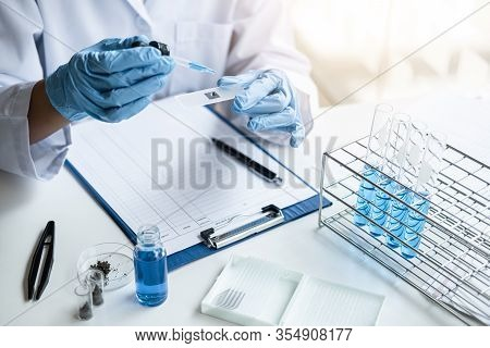 Scientist Or Medical In Lab Coat Holding Test Tube With Reagent, Mixing Reagents In Glass Flask, Gla