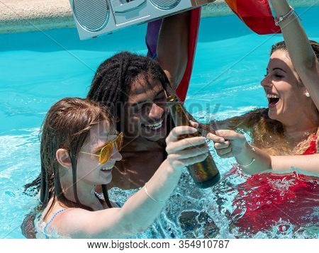 Stock Photo Of A Group Of Young People From Different Ethnic Groups In A Swimming Pool Toasting With