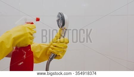 Woman In Rubber Gloves Cleaning The Shower Head. Housemaid Washing Metallic Head Of The Shower. Hous