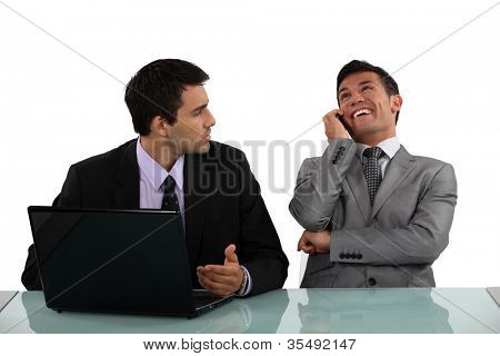Businessman getting annoyed at loud colleague