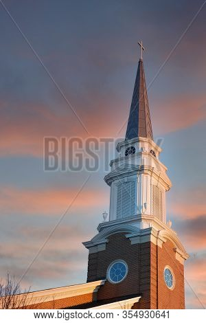A Baptist Church Steeple Rising Into A Clear Blue Early Morning Sky With Half Moon In Background