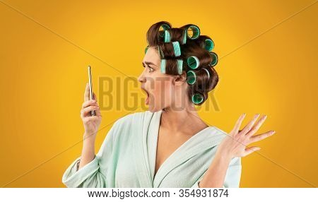 Discontented Housewife Holding Smartphone Reading Message Or Shocking News Standing Over Yellow Stud