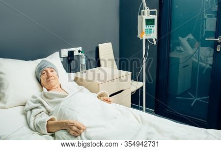 Elderly Woman In A Oncology Clinic Ward Receiving Chemotherapy Treatment. Iv Drip For Chemotherapy