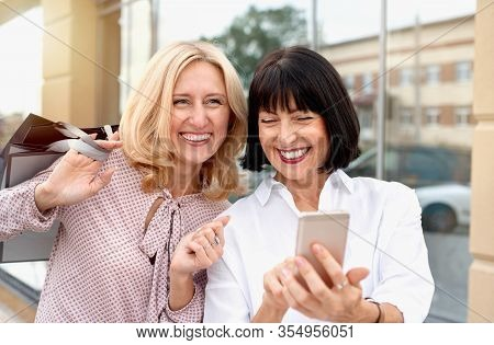 Two Mature Women Looking At The Phone And Having Fun While Doing Shopping