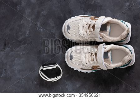 White Kids Sneakers On A Dark Grey Background Flat Lay In Minimal Style. Trendy Sports Shoes, Active