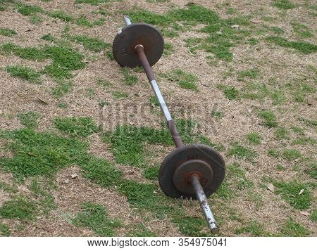 A Bar Bell Sits On The Edge Of A Running Track With A Small Workout Area At A Large Urban High Schoo