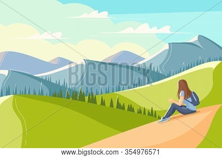 Young Woman Sits On The Grass And Looks At The Mountains
