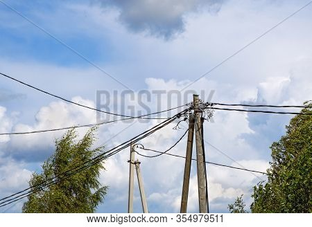 Electric Pole Against The  Background Of Blue Sky. Old Power Lines On A Wooden Pole. Poles And Power