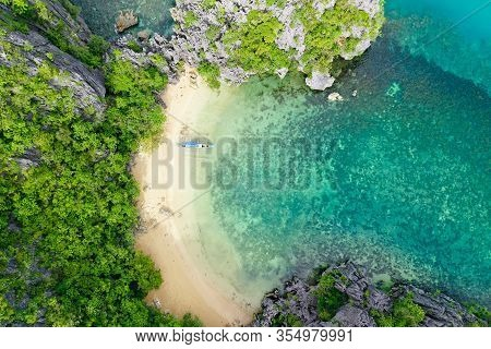 Tropical Island On The Atoll And Turquoise Lagoon. Rocky Island With White Sandy Beach, Aerial View.