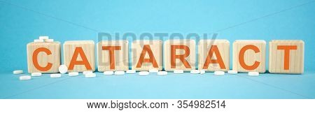 Cataract - Word Made On Wooden Cubes On Light Blue Backround With Tablets (pills) Around. Healthy Ca
