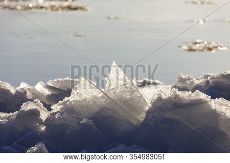 Ice On The Edge Of The Coastline Against The Background Of Water. Thin Ice Near The Shore Of The Riv