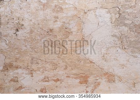 Grunge Background With Old Stucco Wall Texture Of Beige Color. Cracks
