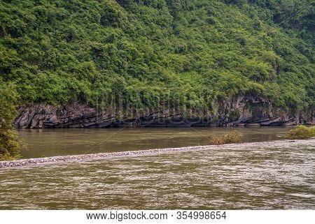 Guilin, China - May 10, 2010: Along Li River. Forested Green Karst Mountain Slope Recede At Bottom O