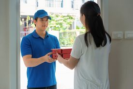 Asian Delivery Young Man In Blue Uniform Smile And Holding Pizza Boxes In Front House And Asian Woma