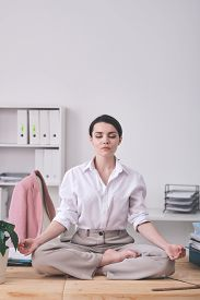 Calm young businesswoman with closed eyes sitting in zen-like position and meditating in office